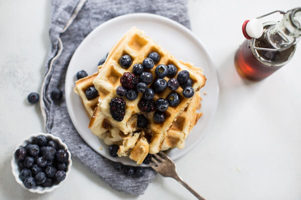 Homemade waffles overhead shot on white background with maple syrup