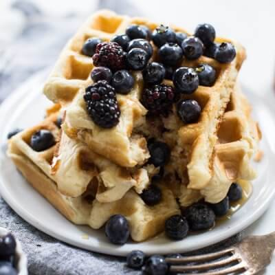 Stack of Belgian waffles on white background with berries and fork