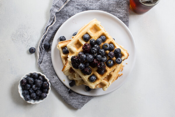 gluten free waffles on white plate with blueberries