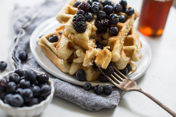 close up bite shot of homemade buttermilk waffles with blueberries
