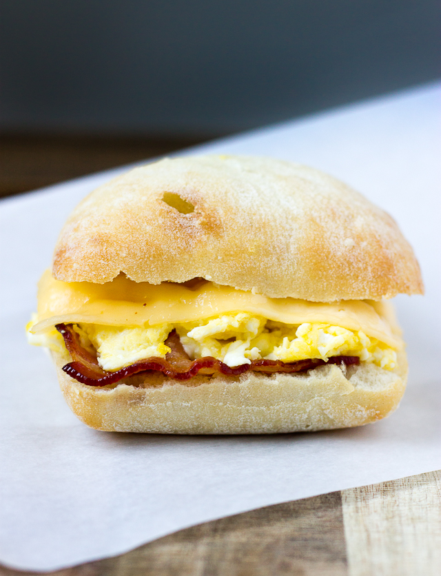 close up of breakfast sandwich with bacon, egg, and gouda cheese on ciabatta roll