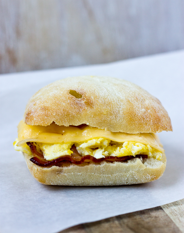 side shot of bacon, egg and gouda cheese breakfast sandwich on ciabatta roll