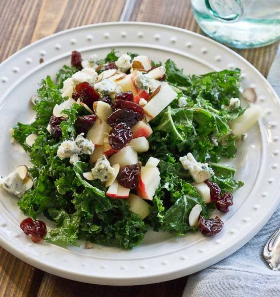 Refreshing Apple & Kale Power Salad topped with tart cherries, almonds, blue cheese, and perfectly dressed with apple maple vinaigrette!