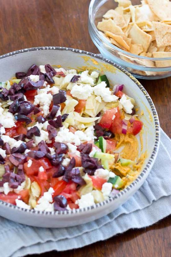 This Greek 7 Layer Dip is loaded with only the good stuff-- roasted red pepper hummus and loads of veggies. Perfect appetizer to serve at any party.