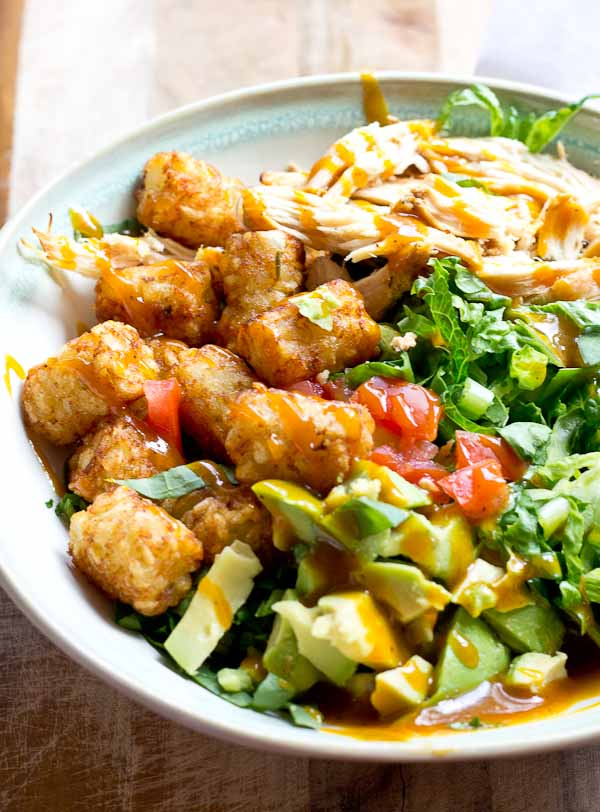 Comfort food meets salad greens. Get obsessed over this salad combo... crispy take-me-back-to-my-childhood tater tots, warm grilled chicken and crunchy shredded greens all smothered in BBQ sauce for the win!