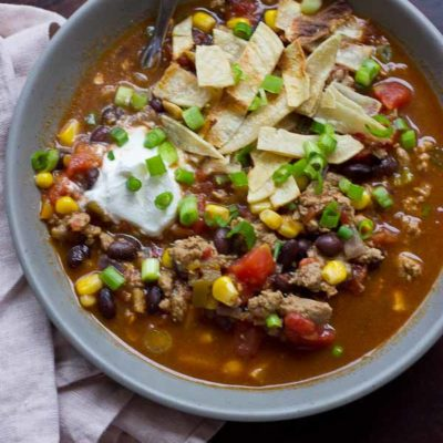 This Turkey Taco Soup is easy peasy to make for a weeknight dinner... a healthy meal the whole family will enjoy. Toss all ingredients into a pot and simmer until you're ready to eat! The toppings are the best part! | @KristinaLaRueRD | www.loveandzest.com