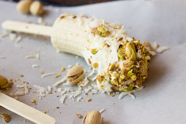 These Banana Crunch Pops are just what you need on a hot summer day, kids and adults rejoice! Only 4 ingredients and very simple to make! Place banana on stick, dunk in Greek yogurt and roll in pistachios and shredded coconut and freeze.