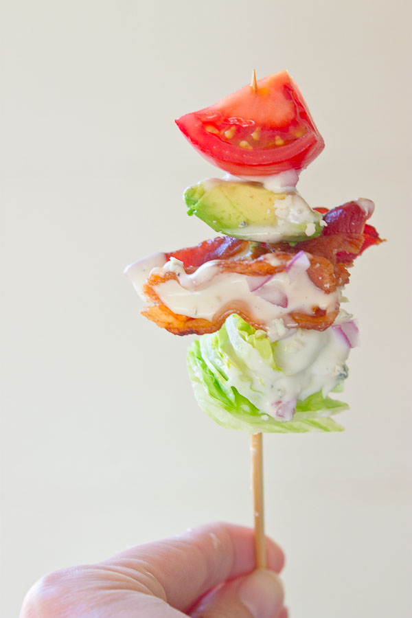 Wedge Salad Skewers…. Iceberg lettuce, crispy bacon, avocado, tomatoes, and blue cheese dressing on a stick. YUM!! This appetizer is perfect at a cookout or anytime you're serving a crowd.