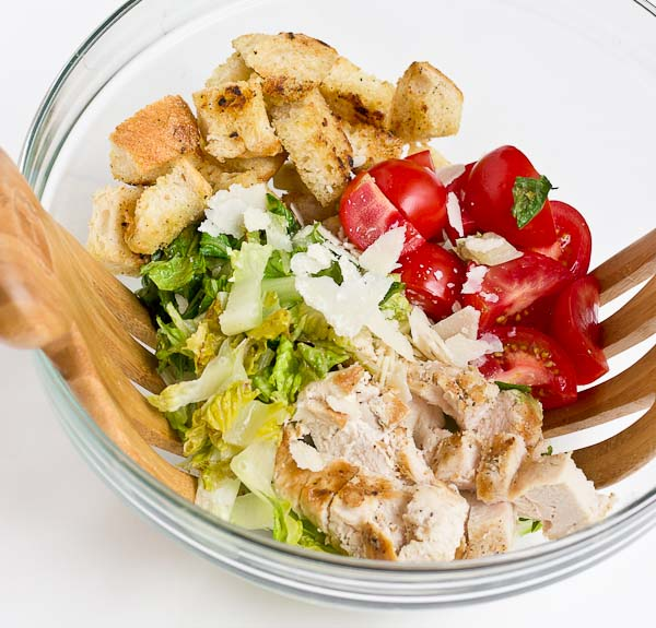 If you love chopped meal salads this Grilled Greens Chicken Caesar Chopped Salad is for you! A healthy caesar salad made with grilled romaine, grilled chicken breast, sweet tomatoes, homemade croutons, and zesty Greek yogurt caesar dressing