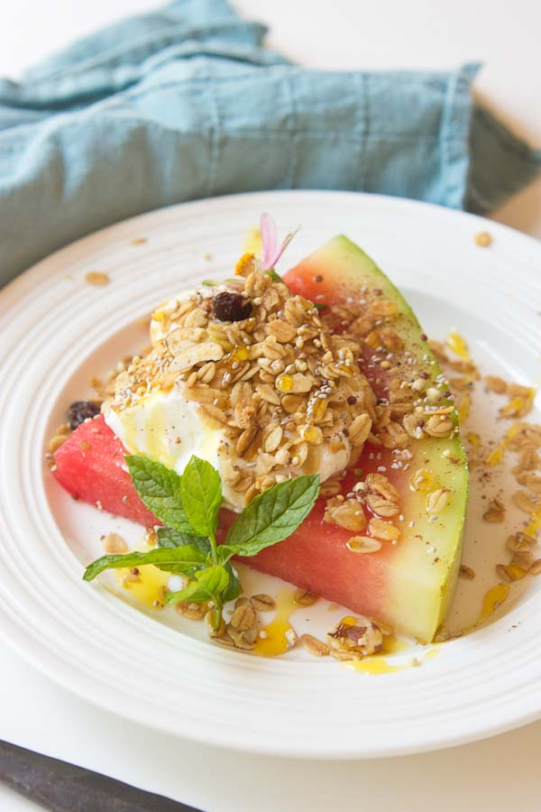 This Watermelon Breakfast Pizza is so it guys! Slice of watermelon, topped with Greek yogurt, seeds, and a drizzle of honey. Make it your own by adding your favorite toppings. The possibilities are endless.