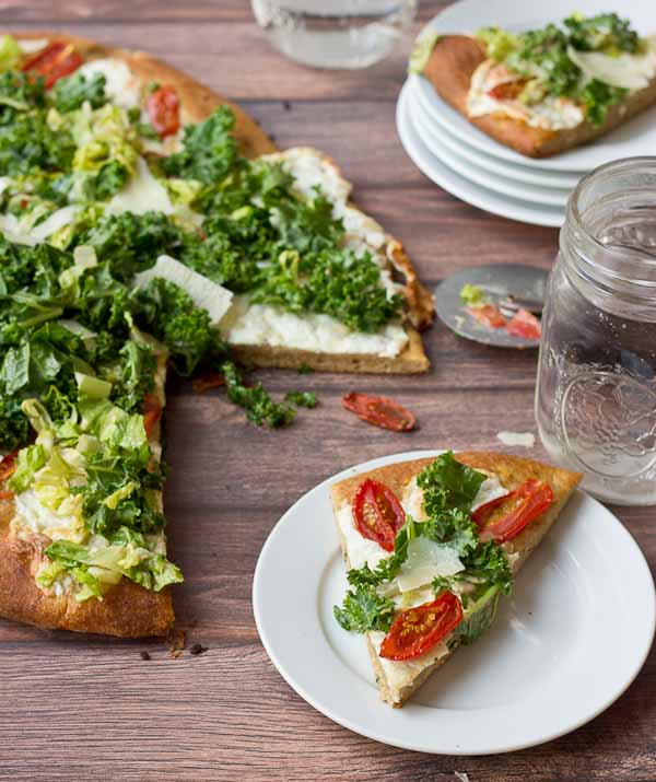 Get your Kale Caesar Salad Pizza on!! This pizza will be the talk of the town, a delicious Pizza blanca with roasted tomatoes, garlic and fresh mozzarella topped with loads of Kale Caesar Salad.