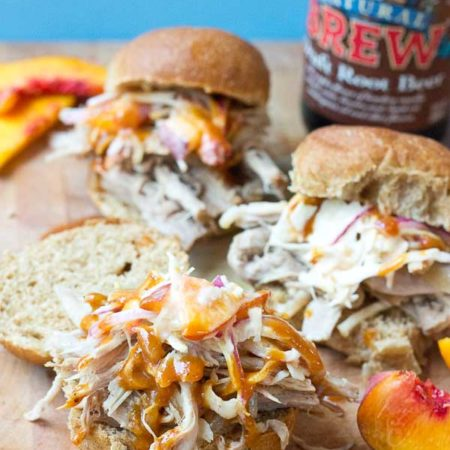 Root Beer Pulled Pork with Peach Slaw made in the slow cooker just in time for game day! This recipe has a simple ingredient list and that Homemade BBQ Sauce and those peaches in that Peach Slaw, you can't miss out on that sweetness. YUM!