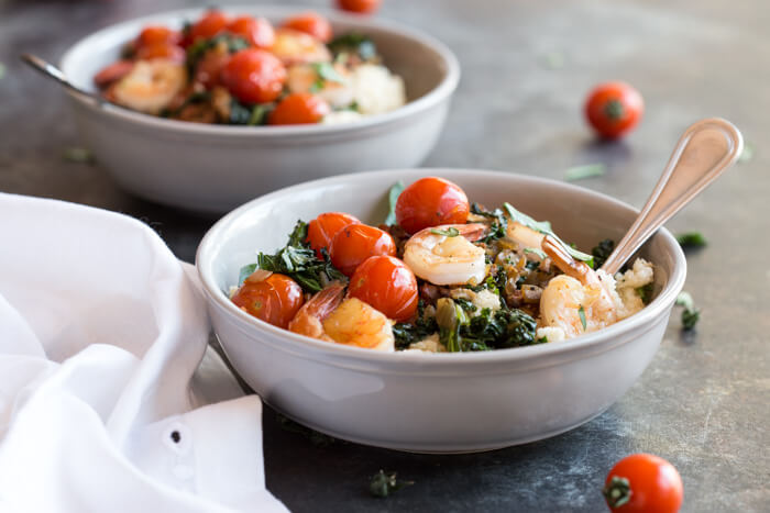 Shrimp and Cheesy Cauliflower Grits, a low carb southern breakfast. Cheesy cauliflower grits topped with savory shrimp, bacon, a hearty dose of kale, and blistered cherry tomatoes.