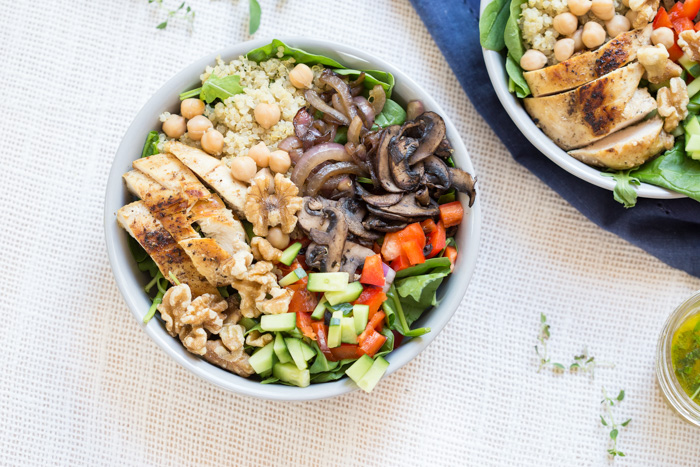 bowl is topped with grilled chicken, sautéed onions and mushrooms and a zesty herb dressing.