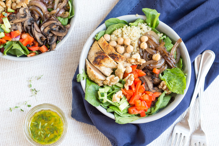 The perfect summer salad has grilled ingredients served warm served with fresh raw veggies. This Mediterranean Quinoa Chicken Salad bowl is topped with grilled chicken, sautéed onions and mushrooms and a zesty herb dressing.