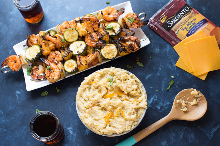 A classic southern dish gets a smoky twist with these Smoky Cheddar Cauliflower Grits and Cajun Shrimp. Cheesy cauliflower grits are served alongside sweet and spicy shrimp skewers with zucchini and pineapple.