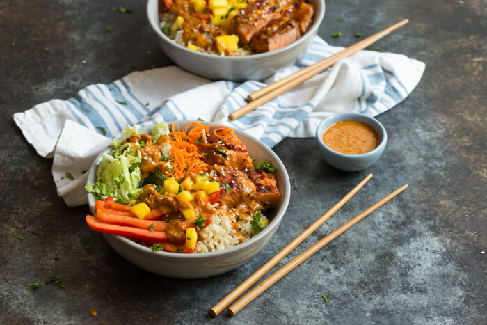 Spicy Thai Salmon Grain Bowls loaded with veggies, brown basmati rice and warm baked salmon and a drizzle of spicy Thai sauce.... because everything is better in bowl form.