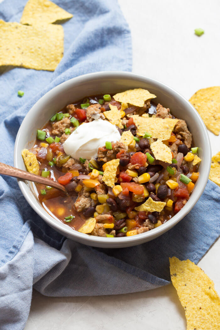 This Turkey Taco Soup is easy peasy to make for a weeknight dinner... a healthy meal the whole family will enjoy. Toss all ingredients into a pot and simmer until you're ready to eat! The toppings are the best part!