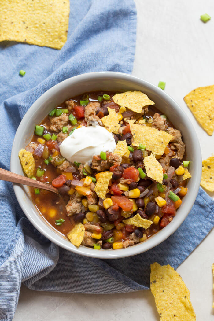overhead shot of turkey taco soup with crushed tortilla chips and sour cream