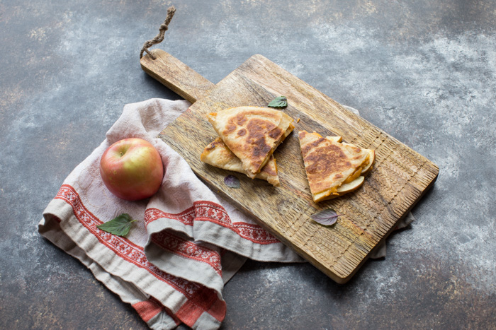 If you're looking for a simple comfort food dinner (or lunch) that tastes like fall-- this is it! Creamy Pumpkin Apple Quesadillas are perfect for little hands for snacking after school or before trick or treating.