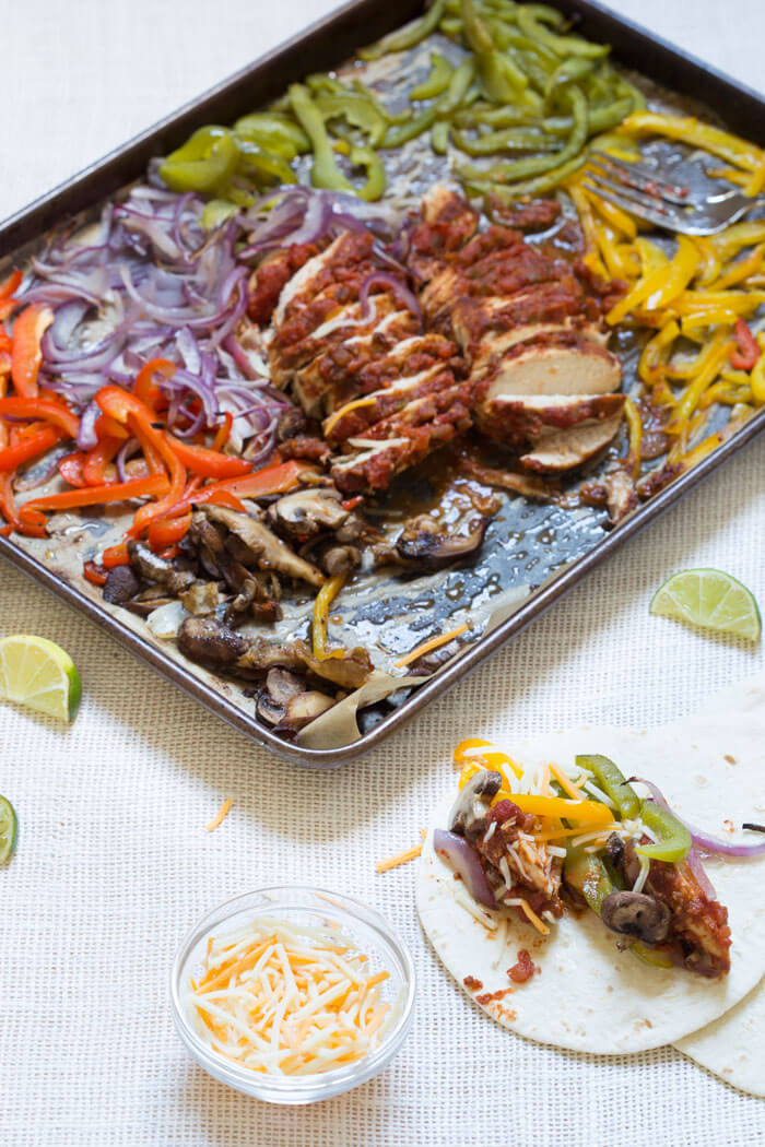 Sheet Pan Chicken Fajitas are our new weeknight dinner wonder. Check it, all the fajita veg plus super moist flavor packed chicken loaded on one pan and baked in the oven... then wrapped in soft tortillas and topped with cheddar, sour cream and avocado. What's not to love?