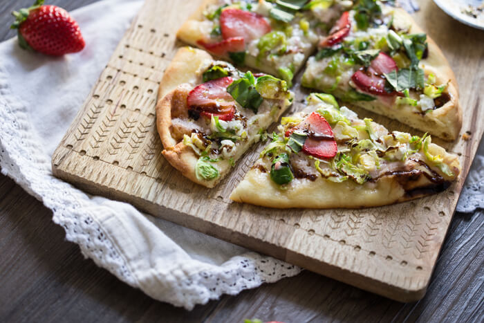 Strawberry Brussels Sprouts Naan Flatbread an easy appetizer or main made that's sweet and savoy. Warm naan bread loaded with shaved Brussels sprouts, strawberry mascarpone, fresh strawberries, and a tangy balsamic drizzle. So good.