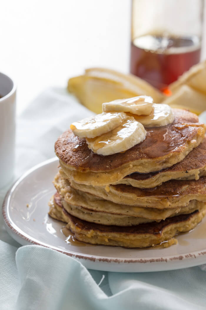 close up shot of paleo banana coconut flour pancakes with maple syrup