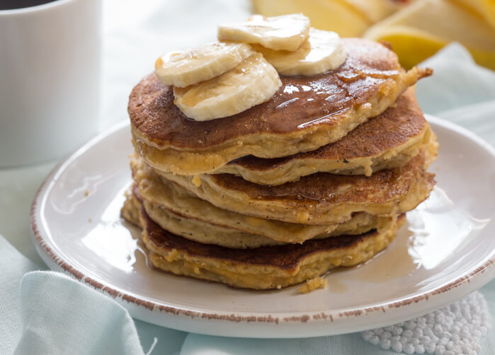 side shot of paleo banana coconut flour pancakes with sliced bananas and maple syrup