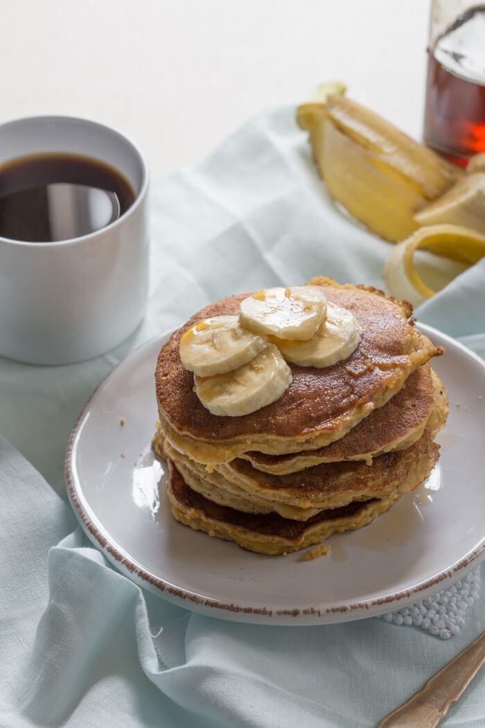 overhead shot of paleo banana coconut flour pancakes with sliced bananas and maple syrup