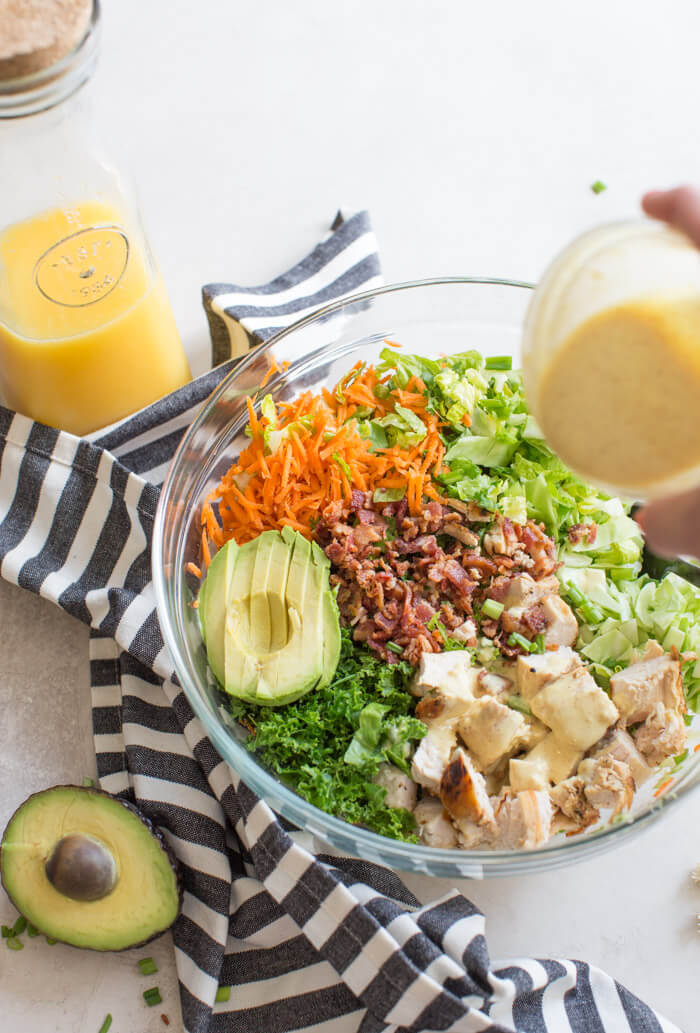 OH ME OH MY! This Farmhouse Chicken Chopped Salad with romaine, cabbage, kale, carrots, grilled chicken breast, bacon, sunflower seeds and avocado tossed in a tangy orange honey mustard dressing is my jam.