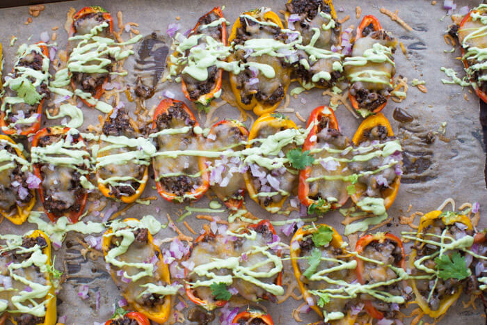 Mini Bell Pepper Nachos with Avocado Cream made on a sheet pan. These plant based mushroom loaded nachos with cool avocado cream are a veggie lovers dream.