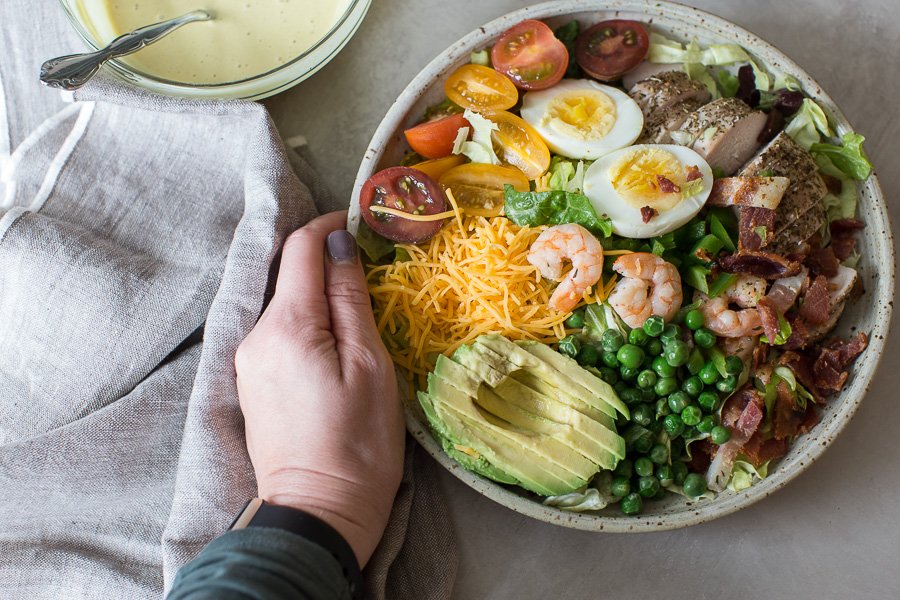hand holding bowl of healthy cobb salad recipe and cobb salad dressing