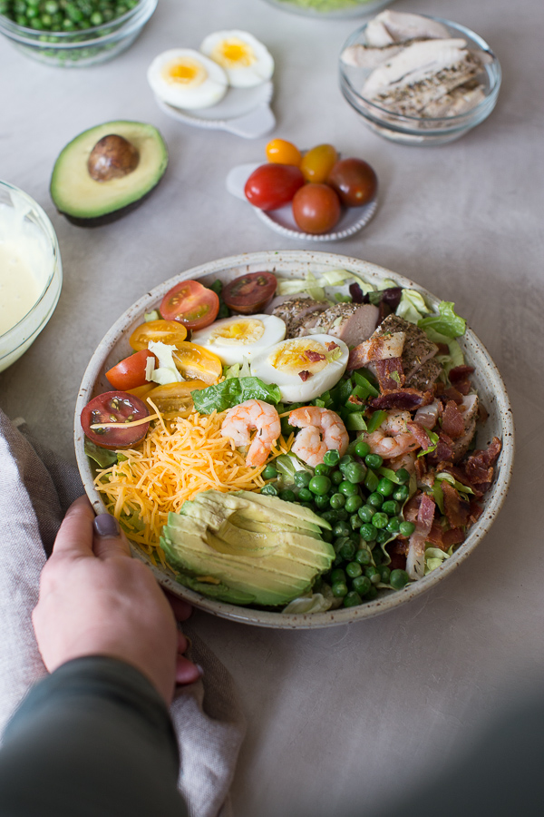 hand reaching in to grab bowl of cobb salad with shrimp and chicken