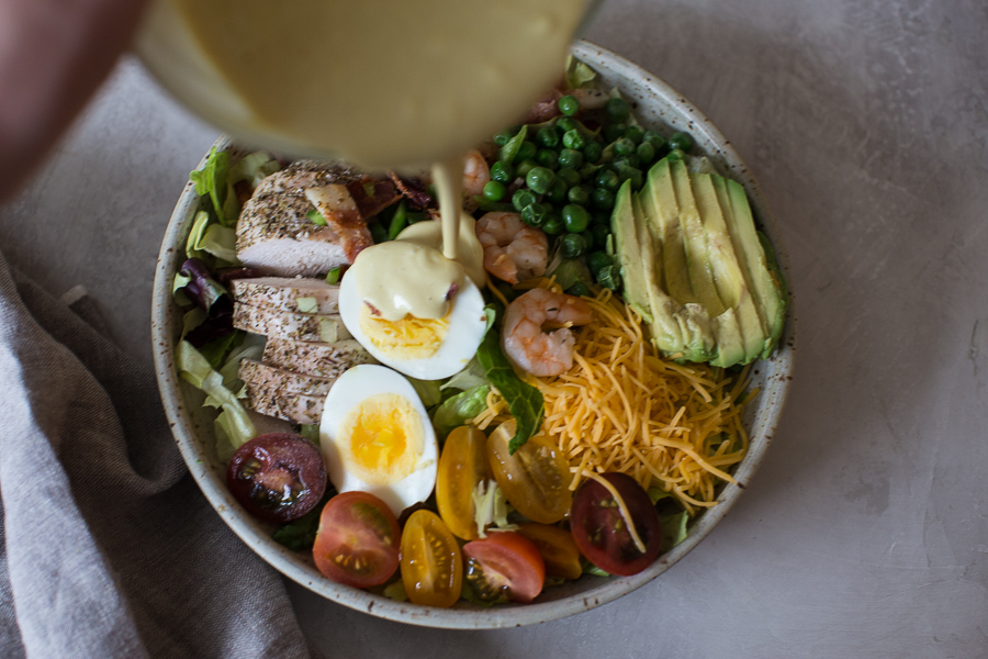 Overhead shot of healthy cobb salad recipe with eggs, bacon and avocado on an white background