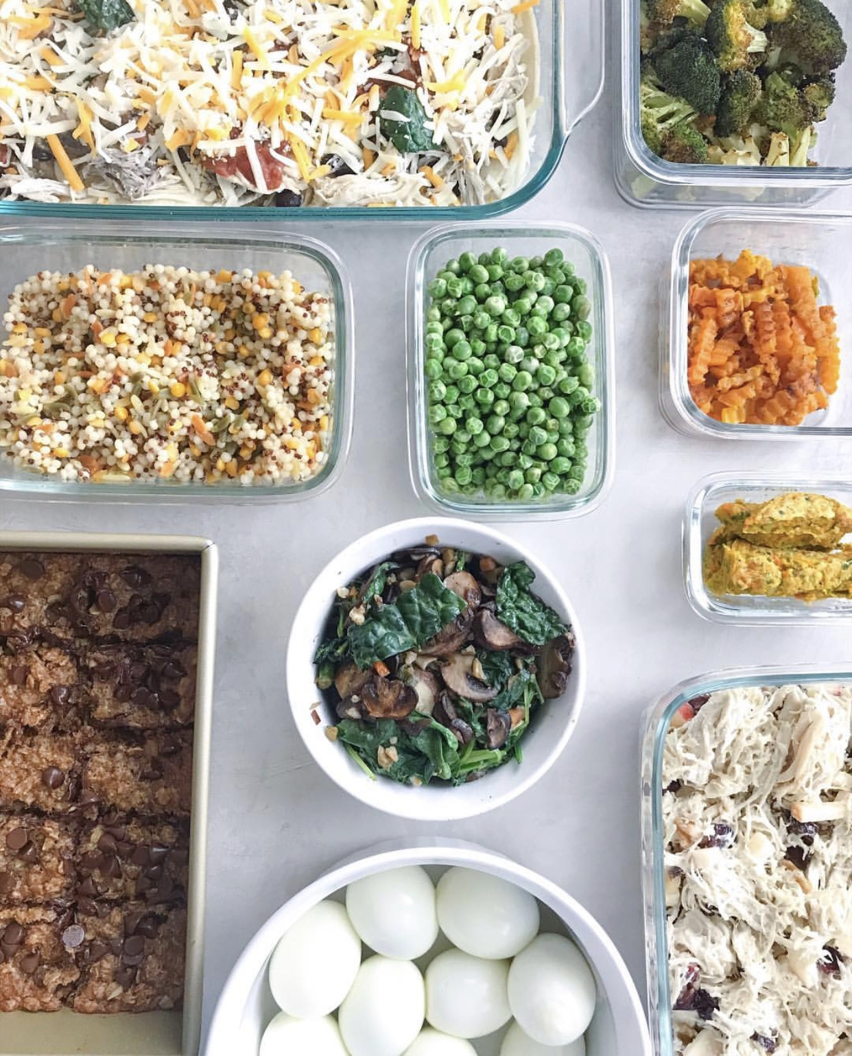 overhead shot of healthy meal prep with casserole, bars, eggs, chicken salad