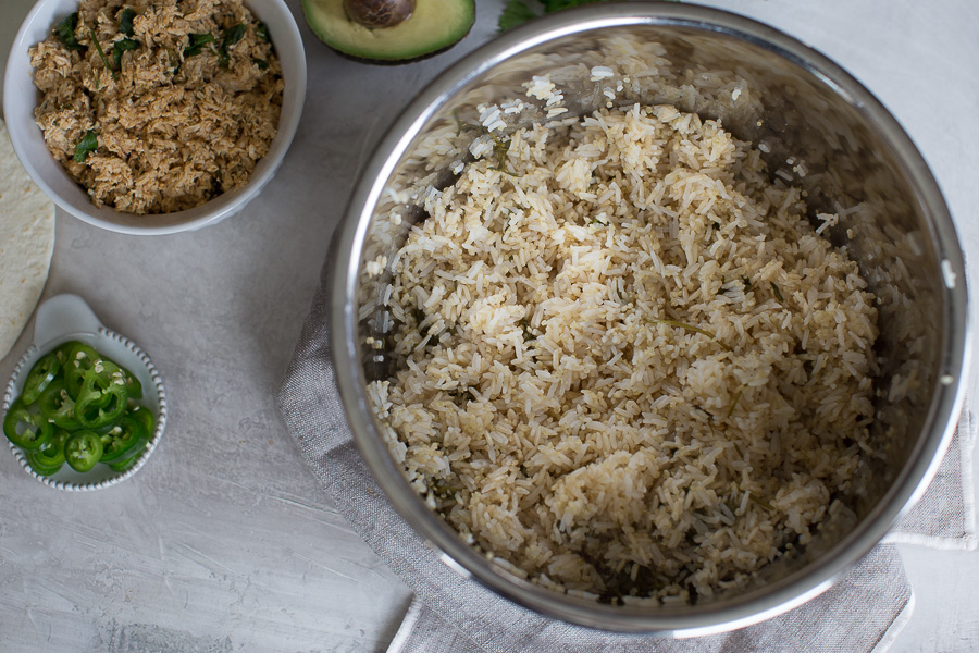 Overhead shot of cilantro lime rice in the Instant Pot with side of jalapenos, shredded chicken and avocado