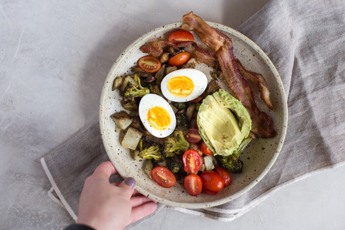 soft boiled eggs in ceramic bowl with avocado, bacon, potatoes and tomatoes