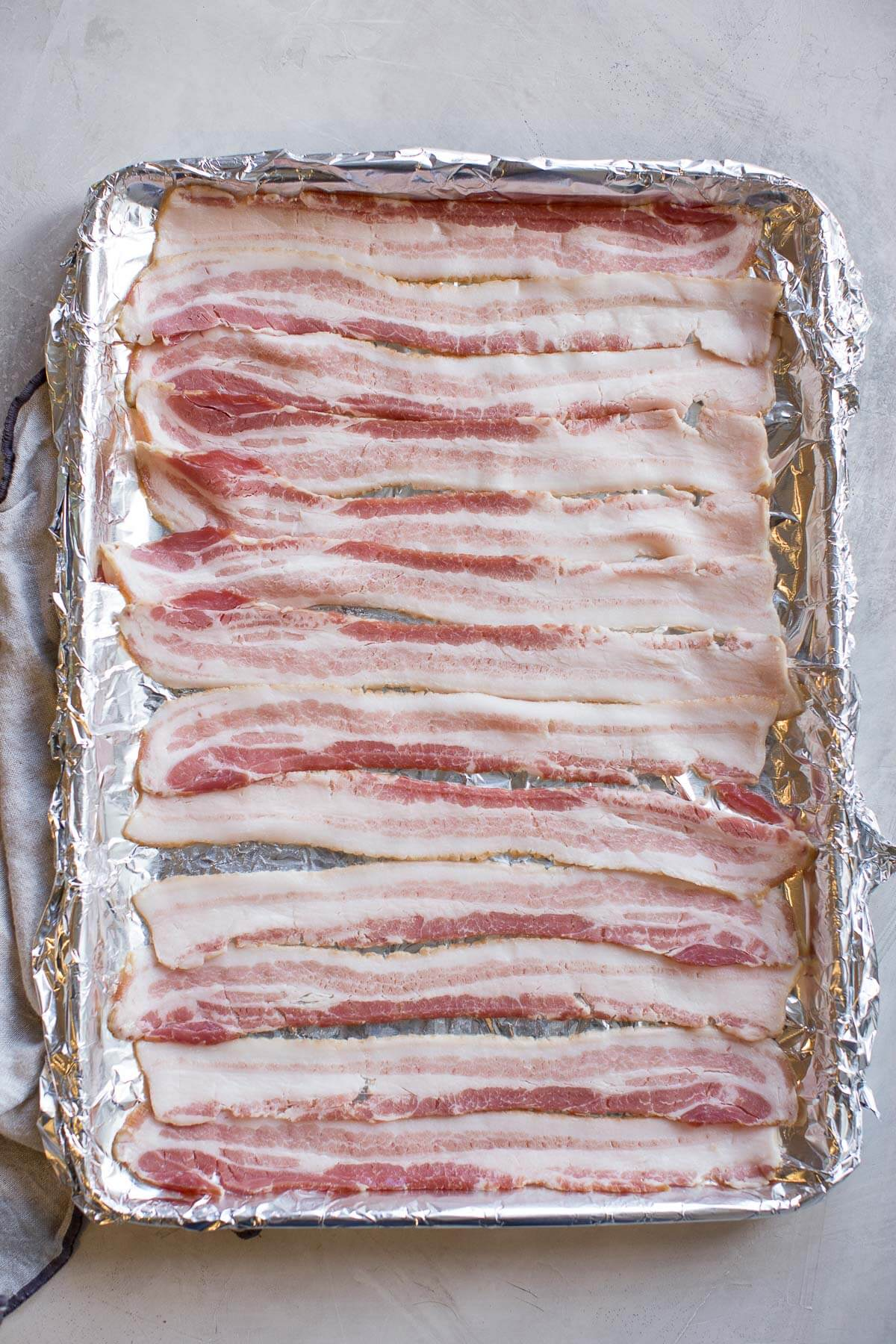 uncooked bacon on baking sheet about to go in oven