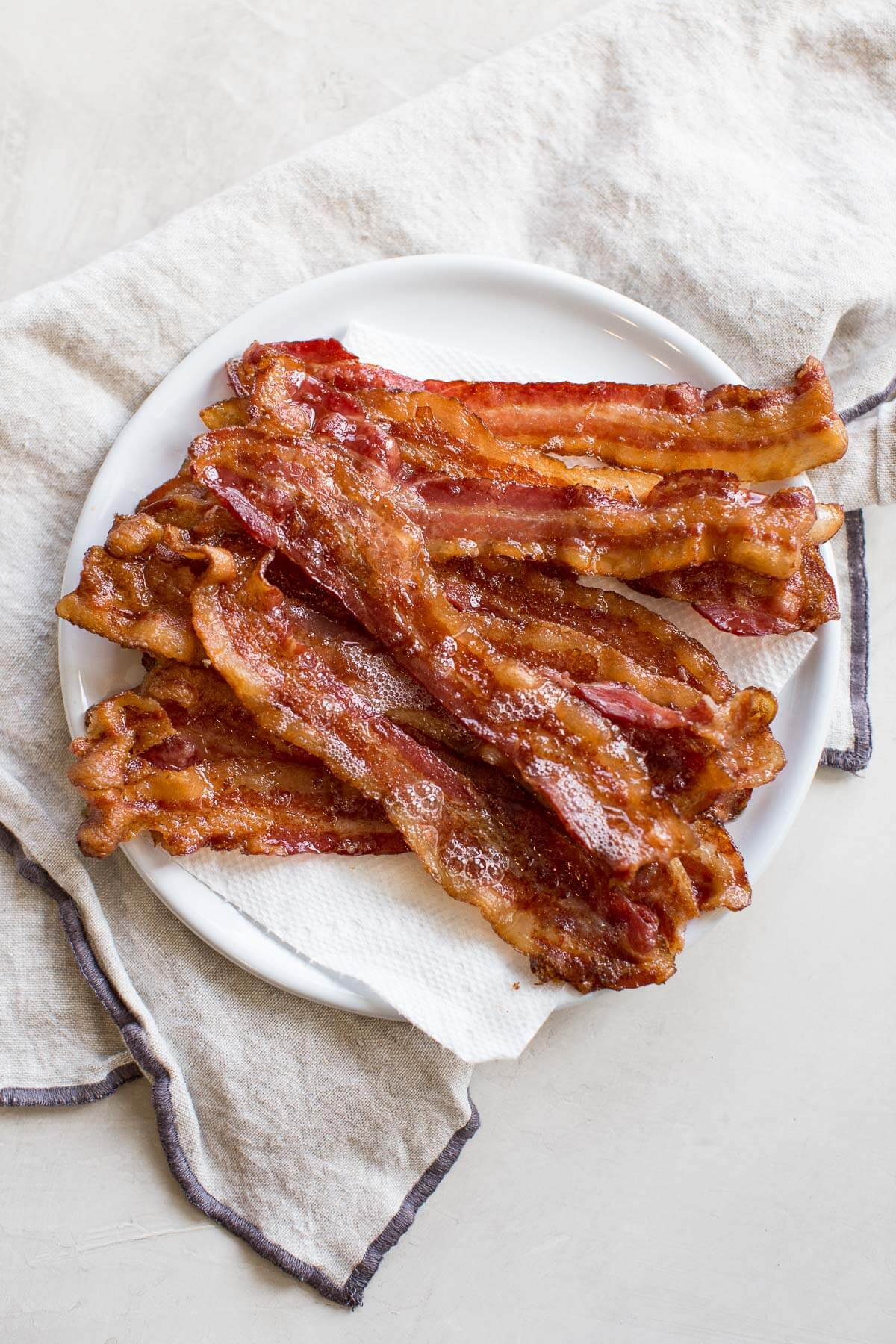 plate of bacon on paper towels after cooking bacon in the oven