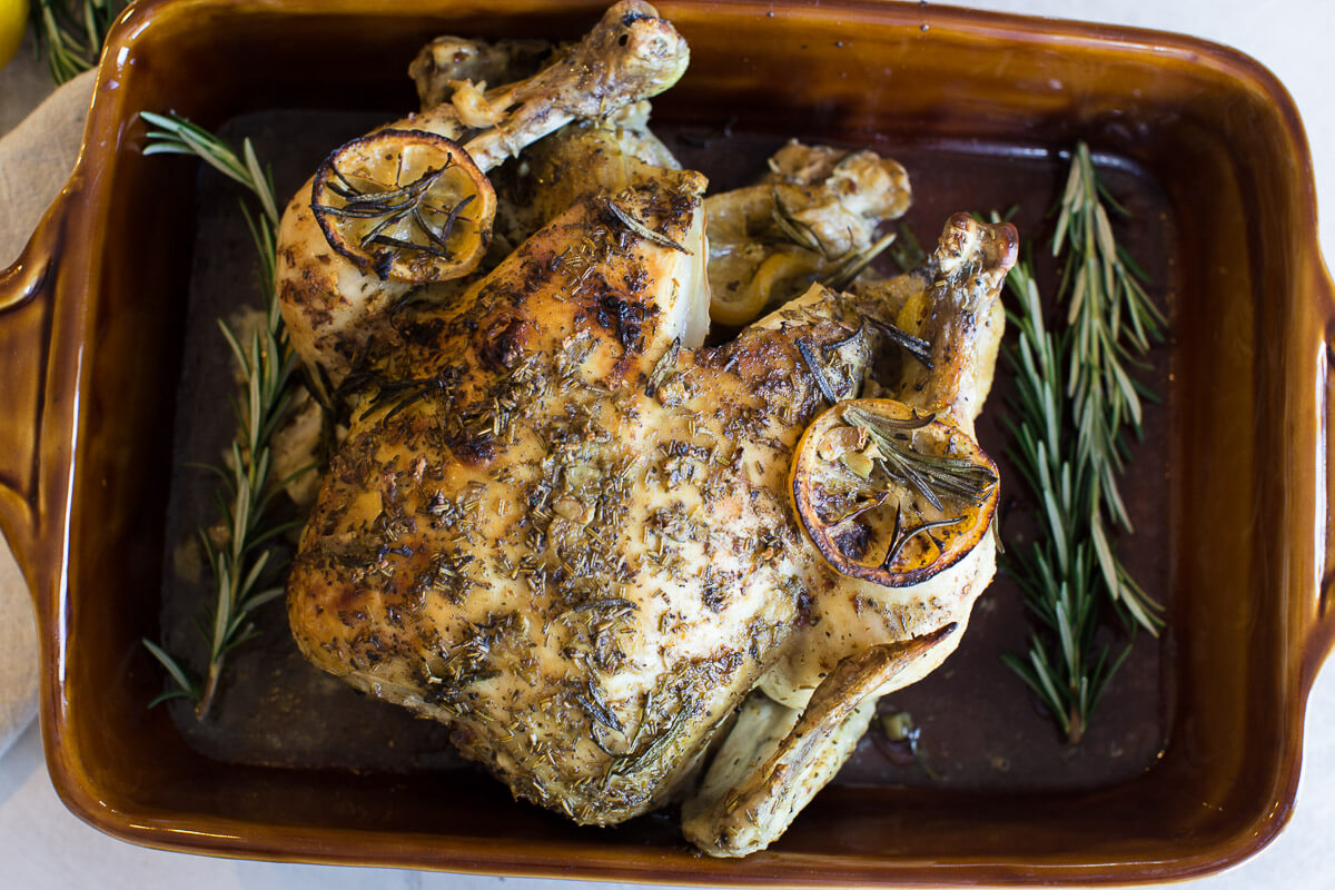 overhead shot of cooked whole chicken with fresh rosemary and lemons