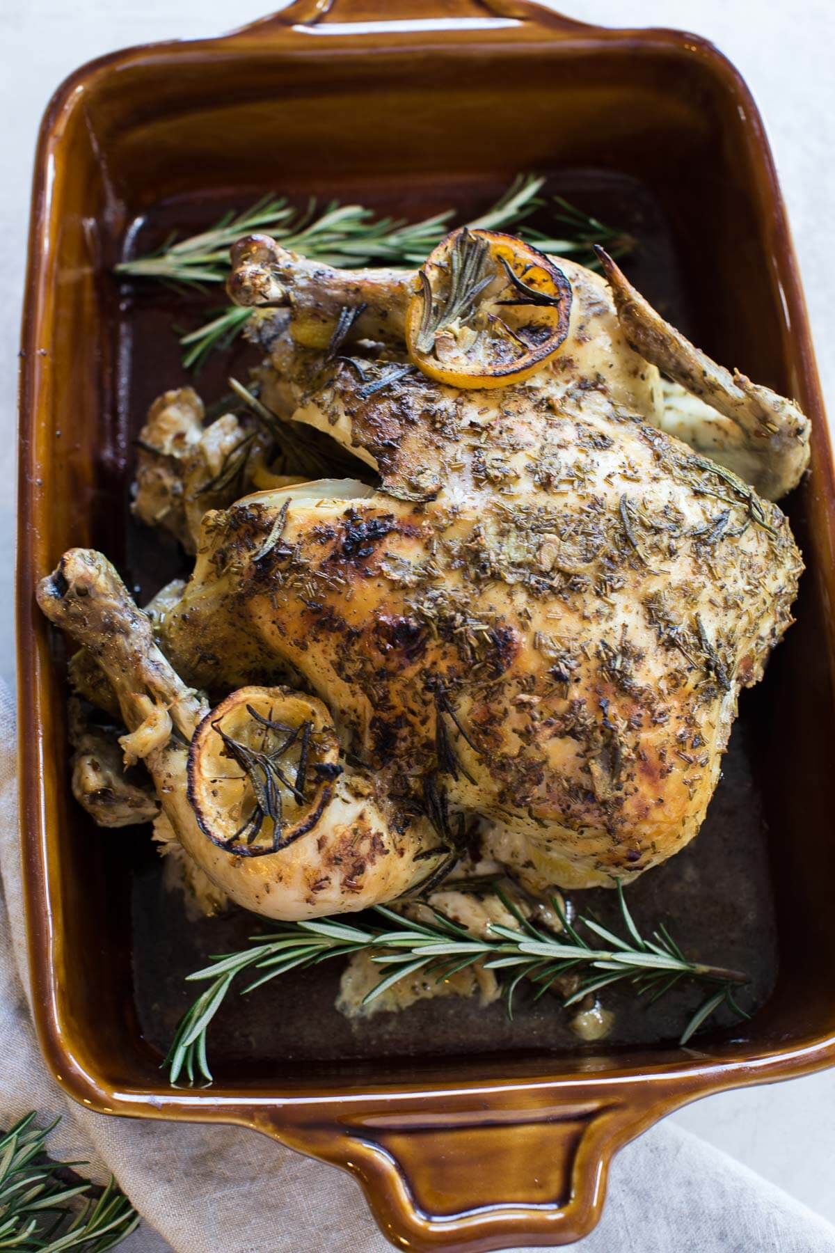 overhead shot of cooked whole chicken with rosemary sprigs, fresh herbs and lemon slices