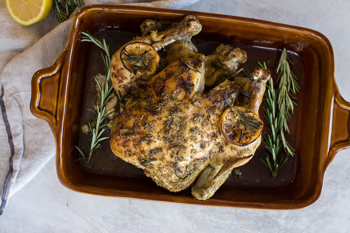 overhead shot of cooked whole chicken with fresh rosemary and lemon