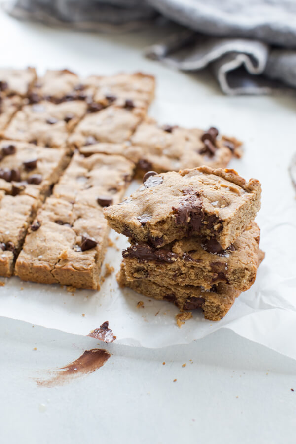 Side shot of two stacked almond butter blondies with a chewy and chocolatey center