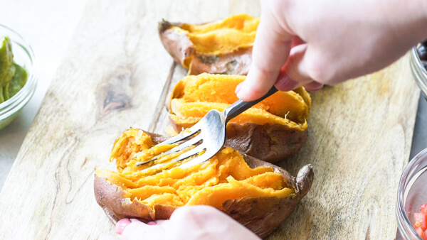 This Slow Cooker Carne Asada recipe is so easy to make with an authentic carne aside marinade stuffed into a microwaved sweet potato. Genius!