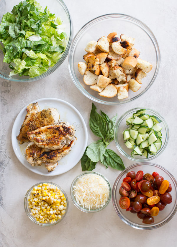 """End of Summer"" Chicken Panzanella Salad recipe made with fresh tomatoes, cucumbers, chunks of toasty garlic bread, grilled corn, fresh basil, avocado, parmesan cheese. It's packed with perfectly seasoned grilled chicken for satiating protein and smothered in a thick balsamic vinegar. YUM!"
