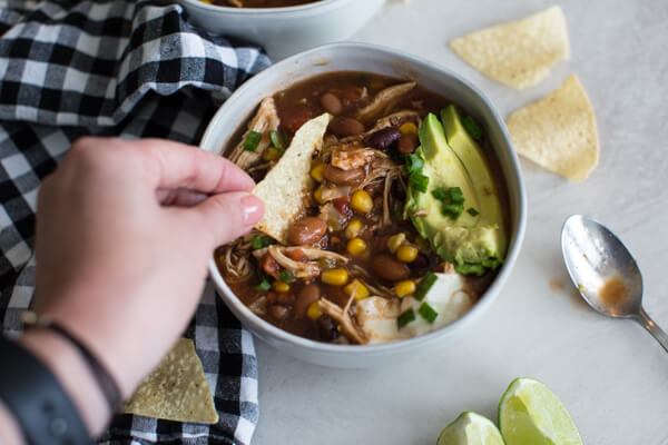 Easy chicken enchilada soup recipe is great for meal prep and freezes well. Can be made in the slow cooker too! Healhty fall comfort food chili recipe FTW!